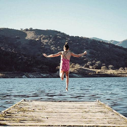 Girl Jumping Off Wharf Into Water
