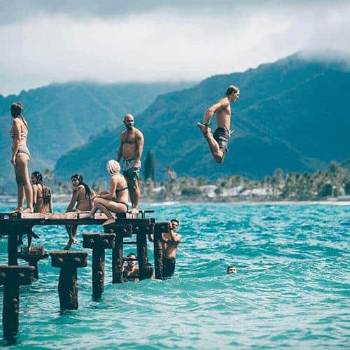 People Jumping Off A Wharf